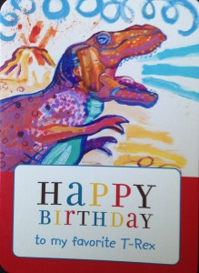 A birthday card with a boy inside a roaring T-Rex.